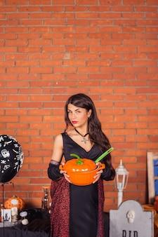 Kobieta w stroju wiedźmy halloween z patelni jak dynia. dekoracje domowe na halloween i wiadro z dynią na cukierek albo psikus.