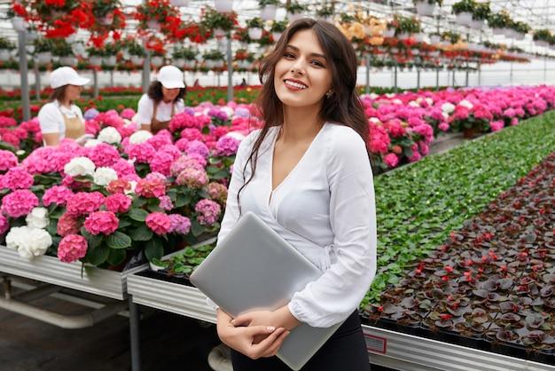 Kobieta w stroju wizytowym trzymająca laptopa w szklarni