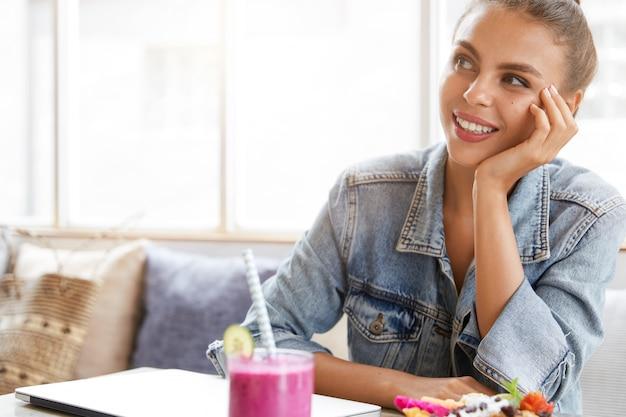 Kobieta w stylowej dżinsowej kurtce w kawiarni