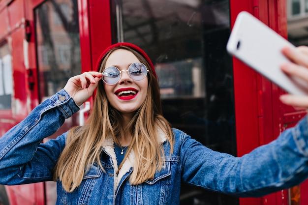 Kobieta w stylowej kurtce dżinsowej przy użyciu telefonu do selfie i śmiejąc się.