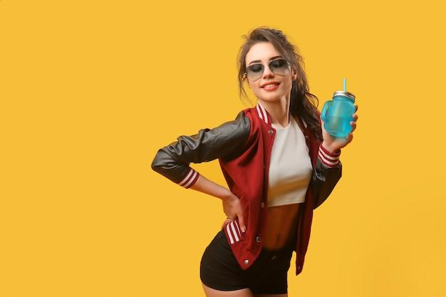 Kobieta w stylowej kurtce ze słoikiem do picia