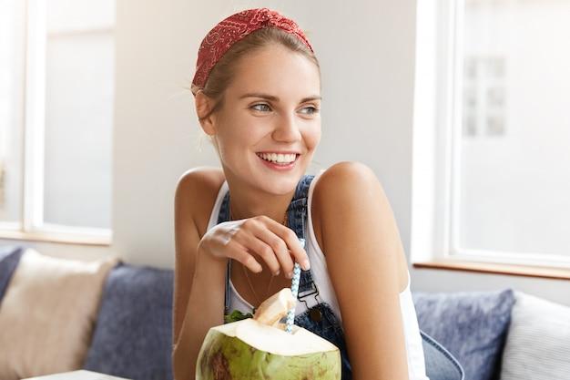 Kobieta w stylowych drelichowych kombinezonach w kawiarni
