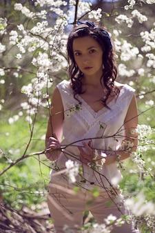 Kobieta w stylowych ubraniach stoi po południu wiosną wśród kwitnących jabłoni