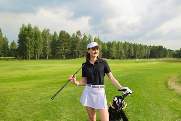 Kobieta w stylowym letnim stroju golfowym spacerująca z torbą kierowców na pięknym zielonym polu do gry w golfa.
