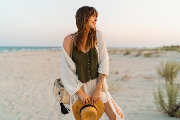 Kobieta w stylowym stroju boho, trzymając słomkową torbę i kapelusz pozowanie na tropikalnej plaży.