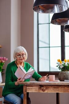 Kobieta w stylowym zielonym swetrze i okularach trzymająca otwartą księgę biblii