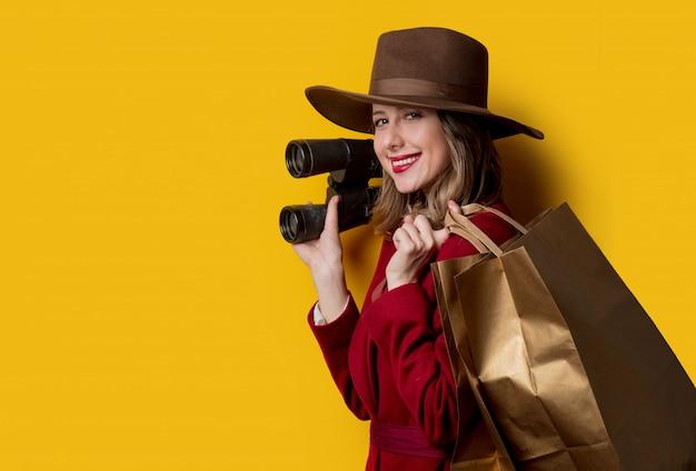 Kobieta w stylu lat czterdziestych xx wieku z lornetką i torbami