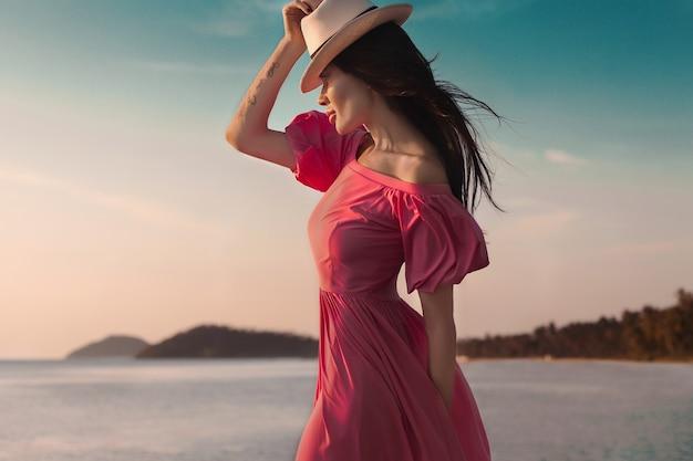 Kobieta w stylu lato na świeżym powietrzu, słoneczny moda portret zmysłowej kobiety nosić różową sukienkę na plaży o zachodzie słońca nad brzegiem morza