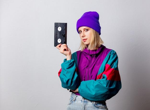 Kobieta w stylu punk z lat 90. z kasetą vhs