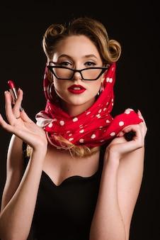 Kobieta w stylu retro z czerwoną szminką na czarnym tle. portret pinup