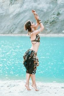 Kobieta w stylu tribal w pięknej biżuterii stoi na brzegu błękitnej plaży morskiej