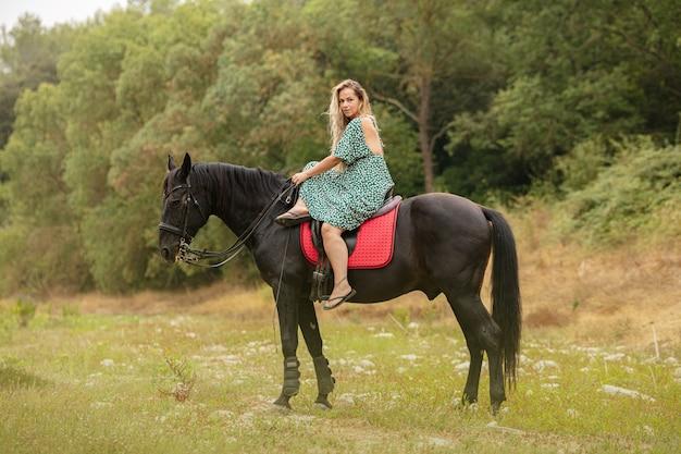 Kobieta w sukience jeździ amazonką na czarnym koniu po bezdrożach
