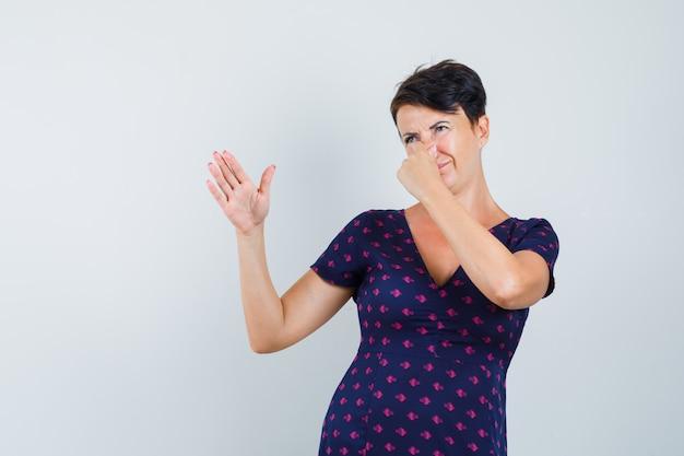 Kobieta w sukience ściska nos z powodu nieprzyjemnego zapachu i wygląda na zniesmaczoną