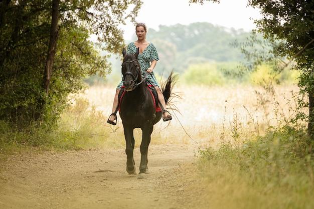 Kobieta w sukience z czarnym koniem w naturze