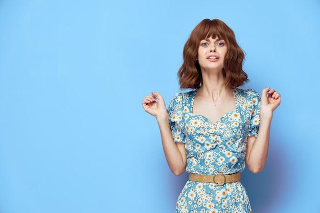 Kobieta w sukni kwiatowej emocje ręce przed tobą grymas krótkie włosy letnie ubrania