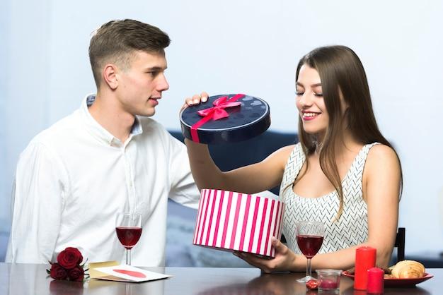 Kobieta w sukni otwarcia prezenta pudełku przy stołem