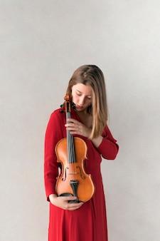 Kobieta w sukni pozuje z skrzypcami