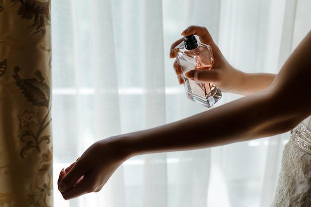 Kobieta w sukni rozpyla perfumy przez delikatny nadgarstek