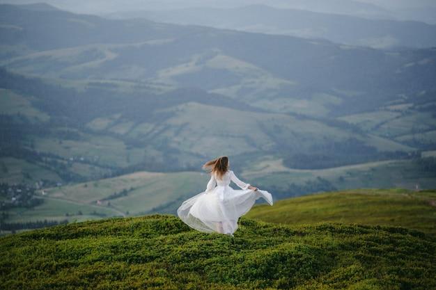 Kobieta w sukni ślubnej biegnie przez pole w kierunku gór