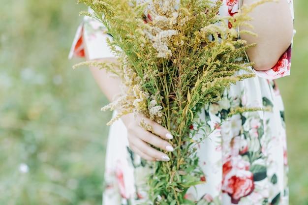 Kobieta w sukni trzyma duży bukiet polne kwiaty