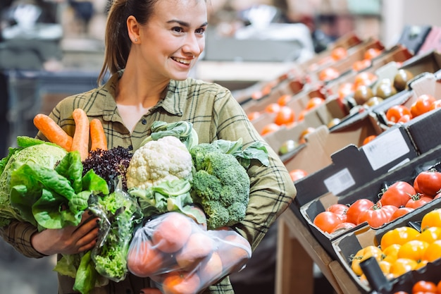 Kobieta w supermarkecie. piękna młoda kobieta robi zakupy w supermarkecie i kupuje świeżych organicznie warzywa