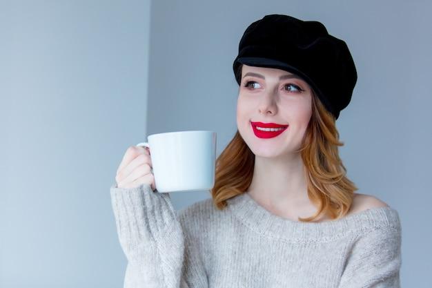 Kobieta w sweter i kapelusz z filiżanką kawy lub herbaty