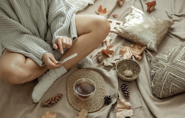 Kobieta w sweterku z dzianiny fotografuje filiżankę herbaty w łóżku wśród szyszek i liści, jesienną kompozycję, zawartość.