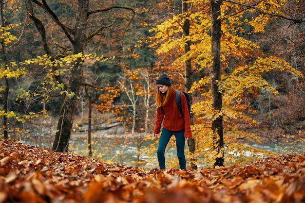 Kobieta w swetrze dżinsy i kapelusz na głowie modelka krajobrazu opadłych liści