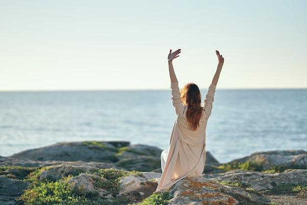 Kobieta w swetrze gestykuluje rękami nad głową w górach w pobliżu morza świeżego powietrza