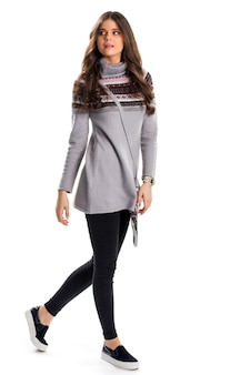Kobieta w swetrze idzie. szary sweter i slipy. nowe obcisłe spodnie. stylowa odzież na chłodne dni.