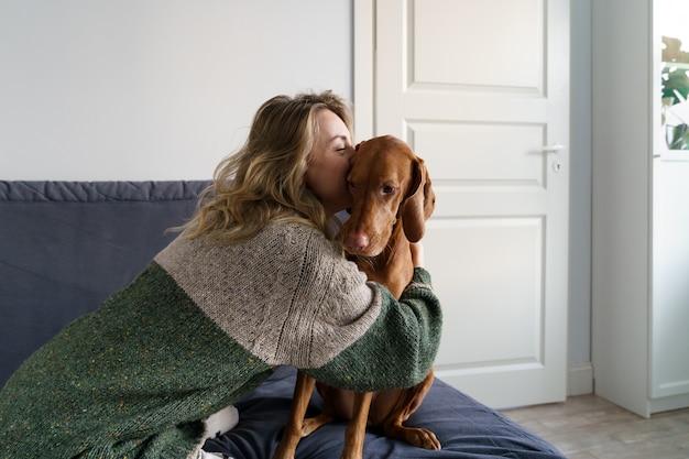 Kobieta w swetrze przytula swojego ukochanego psa wyżeł węgierski krótkowłosy, siedząc na kanapie w domu. kochaj zwierzęta.