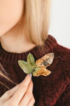 Kobieta w swetrze trzyma chrupiące liście jesienią