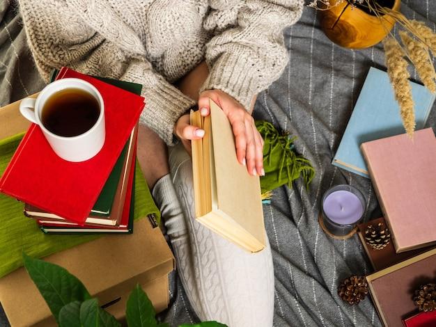 Kobieta w swetrze z dzianiny w otoczeniu wielu różnych książek