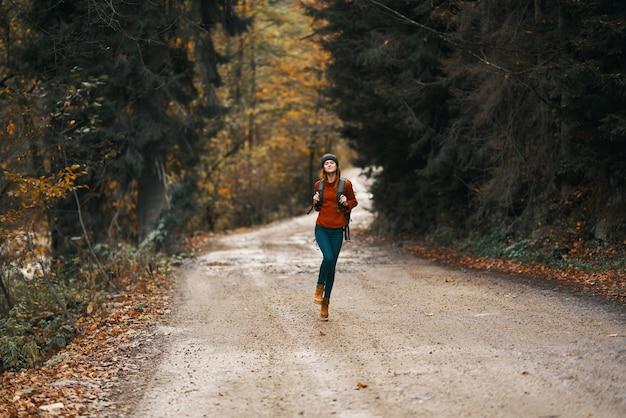 Kobieta w swetrze z plecakiem idzie górską drogą