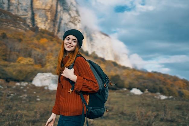 Kobieta w swetrze z plecakiem spaceruje po górach