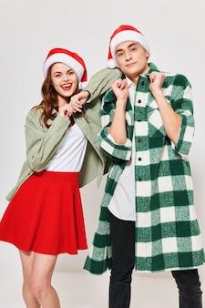 Kobieta w świątecznej czapce opiera się na ramieniu młodego mężczyzny w kraciastej koszuli.