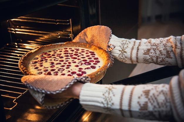 Kobieta w świątecznym swetrze wyjmuje z piekarnika malinowe ciastko.