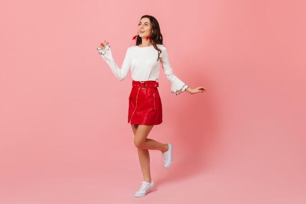 Kobieta w świetnym nastroju biegnie na różowym tle i z podziwem patrzy w górę. pani w stylowej skórzanej spódnicy uśmiechnięta.