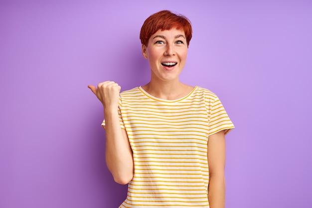 Kobieta w swobodnym stroju, wskazując palcem po bokach, zdjęcie do reklamy. szczęśliwa kobieta pokazuje coś