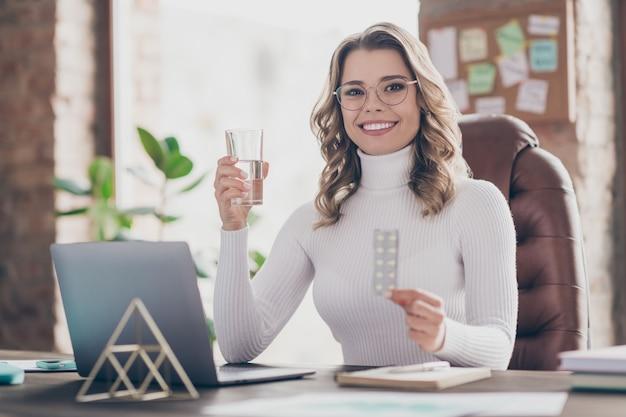 Kobieta w swoim biurze biorąc pigułki