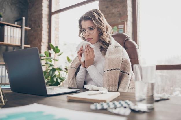 Kobieta w swoim biurze pracuje na laptopie w trakcie jest chora