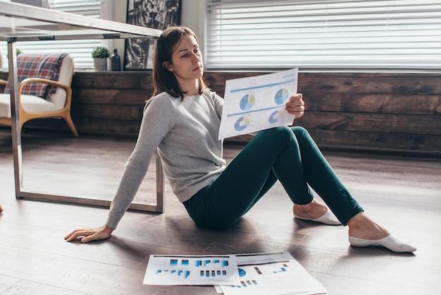 Kobieta w swoim domowym biurze analizuje dokumenty