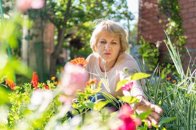 Kobieta w swoim ogrodzie opiekuje się kwiatami i roślinami w słoneczny dzień.