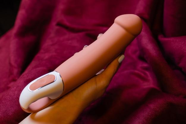 Kobieta w sypialni trzyma wibrator w ręku