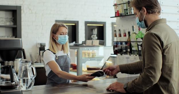 Kobieta w szalonej masce w kawiarni właściciel przedsiębiorca robi kawę dla klienta w kawiarni