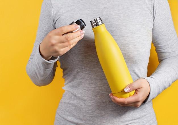 Kobieta w szarej koszulce, trzymając żółtą butelkę z izolacją