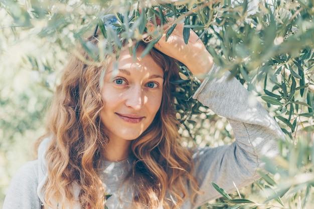 Kobieta w szarej kurtce gospodarstwa oddziału i uśmiechając się w naturze w ciągu dnia