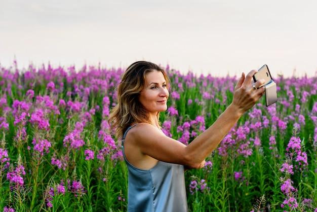 Kobieta w szarej sukience robi selfie zdjęcie na telefon komórkowy na łące fireweed