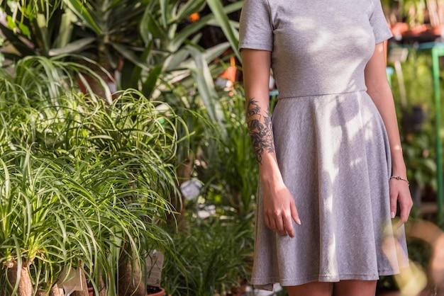 Kobieta w szarej sukni pozyci w zielonym domu