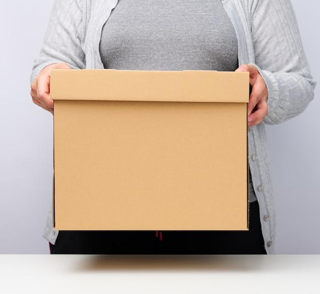 Kobieta w szarych ubraniach stoi i trzyma brązowe pudełko na białym tle, poruszając się, wysyłając i dostarczając towary